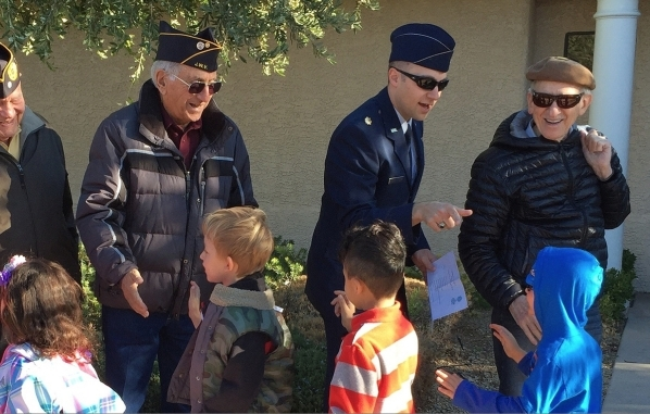 Adelson Educational Campus students high-five veterans and active military Nov. 11 after a flag-raising ceremony on campus. After, the guests told the students true war stories and answered questi ...