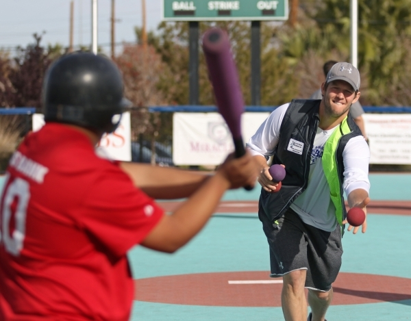 Los Angeles Dodgers' Clayton Kershaw, right, pitches the ball to Nino during a Miracle League of Las Vegas baseball game Saturday, Dec. 5, 2015, in Las Vegas. Kershaw, a 2014 National League ...