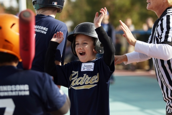 Samuel cheers as he arrives home during a Miracle League of Las Vegas baseball game Saturday, Dec. 5, 2015, in Las Vegas. Clayton Kershaw, a 2014 National League Most Valuable Player, was special  ...