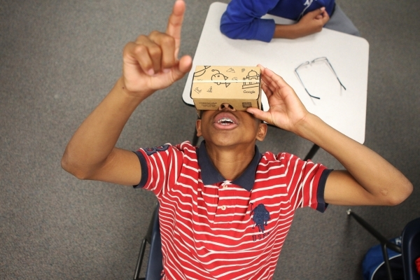 Tayjon Bullock, 14, looks up at a shark using a Google Cardboard headset during a Google Expeditions program class at Leavitt Middle School in Las Vegas Friday, Dec. 4, 2015. The headset allows st ...