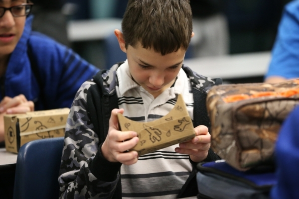 Joshua Snowden, 13, inspects his Google Cardboard headset during a Google Expeditions program class at Leavitt Middle School in Las Vegas Friday, Dec. 4, 2015. The headset allows students to view  ...