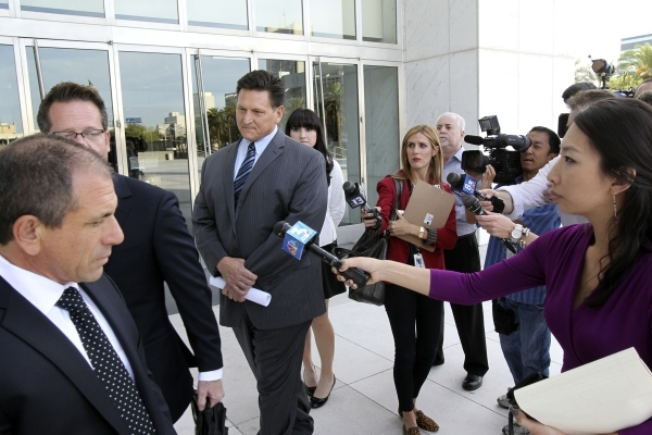 Steven Jones, third from left, declines to talk to the news media Thursday, Nov. 1, 2012, outside the Lloyd George Federal Courthouse in Las Vegas after pleading not guilty to a slew of felony cha ...
