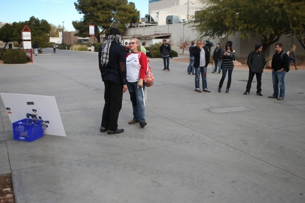 UNLV student Naweed Yusufzai, left, speaks with fellow student Kimberly Bauer after sharing a hug as he stood blindfolded on a walkway at UNLV to promote acceptance, love, and trust for one anothe ...