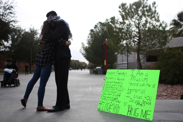 UNLV student Naweed Yusufzai, right, shares a hug with a passerby as he stood blindfolded on a walkway at UNLV to promote acceptance, love, and trust for one another as a Muslim on Friday, Dec. 4, ...