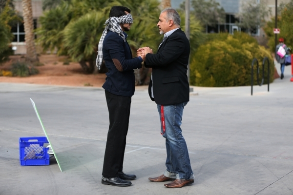 UNLV student Naweed Yusufzai, left, embraces his father Rokai as he stood blindfolded on a walkway at UNLV to promote acceptance, love, and trust for one another as a Muslim on Friday, Dec. 4, 201 ...