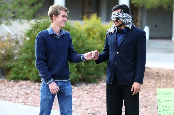 UNLV student Naweed Yusufzai, right, speaks with fellow student Glen Ellefson after sharing a hug as he stood blindfolded on a walkway at UNLV to promote acceptance, love, and trust for one anothe ...