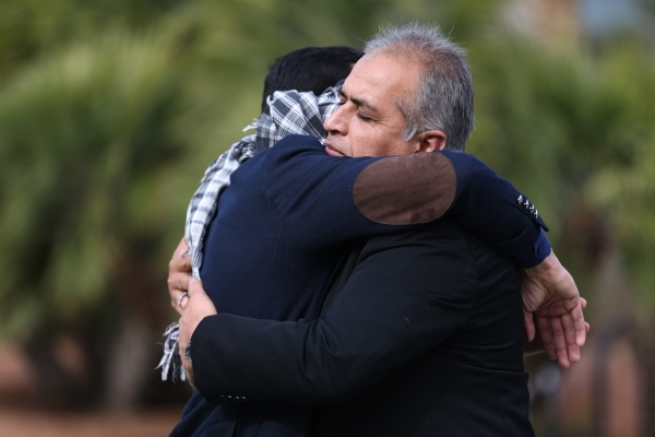 UNLV student Naweed Yusufzai, left, shares a hug with his father Rokai as he stood blindfolded on a walkway at UNLV to promote acceptance, love, and trust for one another as a Muslim on Friday, De ...