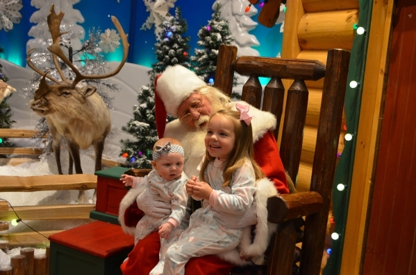 Santa Paul Kudla holds Atlas Cerrone, left, and her aunt Ellisyn Dixon at Bass Pro Shops. Ginger Meurer/Special to View