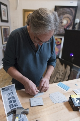 "Artist Daniel Miller prepares labels for his paintings for the art event and charity supply drive ""Third World America"" at EDEN Art Studio & Gallery inside The Arts Factory in Las Ve ..."