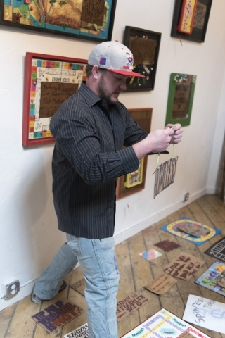 "Artist Justin Lepper prepares a collection of signs for the art event and charity supply drive ""Third World America"" at EDEN Art Studio & Gallery inside The Arts Factory in Las Vegas ..."
