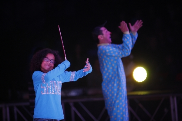 Keira Deleu, left, pretends to play a violin at the instruction of Alex Acero, right, during the opening night for Circus Vargas at the Meadows Mall parking lot in Las Vegas Thursday, Dec. 11, 201 ...