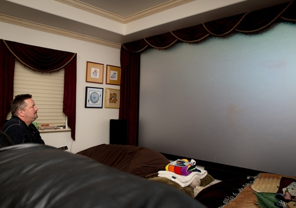 One of the four bedrooms has been converted into a home theater, with red swag window topper curtains around a huge 3-D screen and reclining theater seating for eight, plus large bean bag chairs f ...