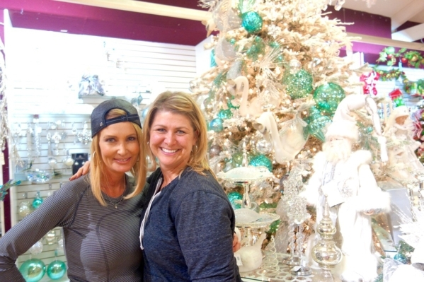 Mindee Garamendi and Jamie Zobrist are part of Ralph Jones Display's design staff. The tree behind them features swans and large teal ornaments on a champagne-colored tree. COURTESY DIANE TAYLOR