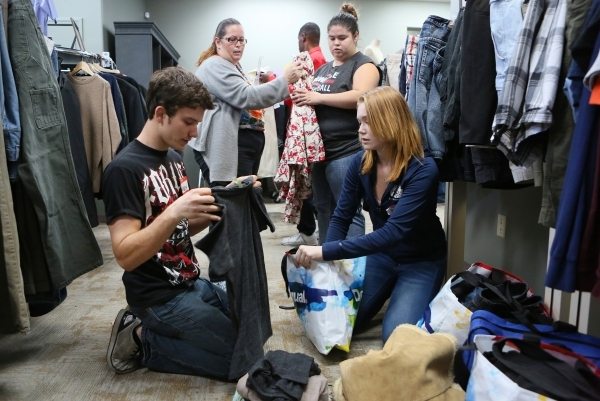 Volunteers Kasey Stevens, front left, and Kate White, front right, pack up items for the children of Juliana Rios, back left, including Rios' daughter Christina Hurley-Castillo, back right,  ...
