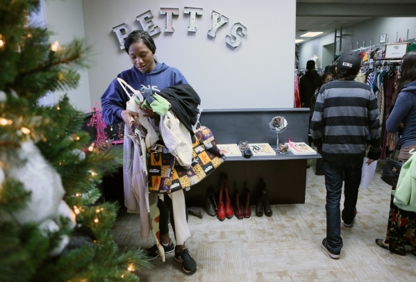 Shopper Haja, last name withheld, left, readjusts the clothes in her hands during a teen shopping day at Project 150 on Saturday, Dec. 12, 2015, in Las Vegas. Project 150 is a nonprofit that allow ...