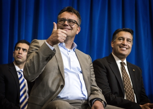 Dag Reckhorn, center, global vice president for Faraday Future, gives a thumps up while sitting with Gov. Brian Sandoval during the  company's announcement   at the Sawyer Building onThursda ...