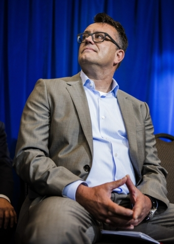 Dag Reckhorn, center, global vice president for Faraday Future, listens while Gov. Brian Sandoval during the  company's  development announcement  at the Sawyer Building onThursday, Dec. 10, ...