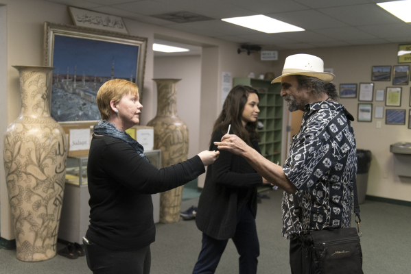 From left, Kara Keating and Ruthie Howard hand a candle to Reverend Joseph Falcone at Jamia Masjid Mosque during an interfaith prayer vigil to remember the victims and the family of the Dec. 2 mas ...
