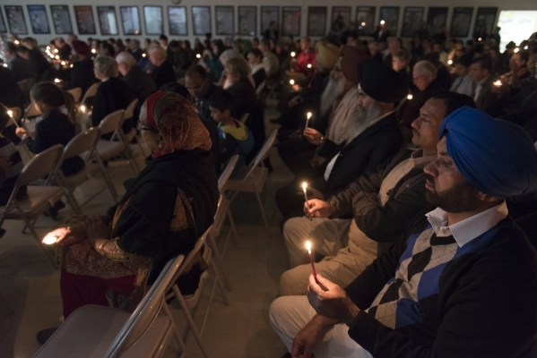 Gurjit Singh, right, holds a lit candle at Jamia Masjid Mosque during an interfaith prayer vigil to remember the victims and the family of the Dec. 2 mass shooting in San Bernardino, California in ...