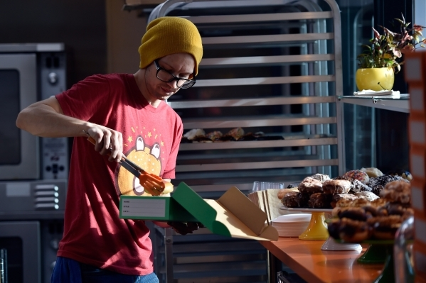 Barista Danny Chandia boxes doughnuts for a customer at the O Face Doughnut shop in Downtown Las Vegas on Monday, Dec. 14, 2015.  The store, backed by the Downtown Project, is set to close later t ...