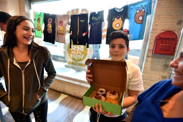 Customers from left, Skylar Walsh, her brother Ethan Walsh and mother, Mary Walsh, smile as Ethan displays their doughnuts at the O Face Doughnut shop Monday, Dec. 14, 2015, in Las Vegas. The stor ...