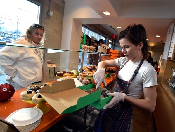 Baker Rachel Bateman, right, boxes doughnuts for Kathy Corson at the O Face Doughnut shop in Downtown Las Vegas on Monday, Dec. 14, 2015.  The store, backed by the Downtown Project, is set to clos ...
