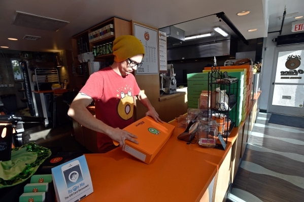 Barista Danny Chandia folds boxes as he waits for customers at the O Face Doughnut shop in Downtown Las Vegas on Monday, Dec. 14, 2015.  The store, backed by the Downtown Project, is set to close  ...