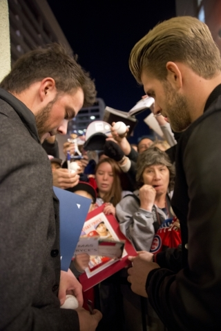 Baseball stars Kris Bryant, National League Rookie of the Year, left, and Bryce Harper, National League MVP, sign autographs after accepting keys to the city from Mayor Carolyn Goodman on the Thir ...