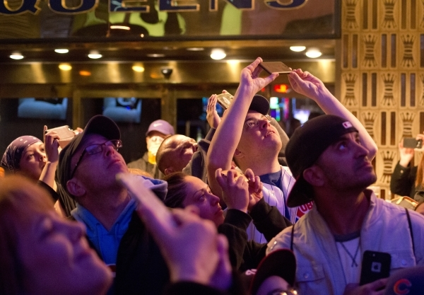 Fans watch a video playing on the Fremont Street Experience canopy highlighting the successes of baseball stars Bryce Harper, National League MVP, and Kris Bryant, National League Rookie of the Ye ...