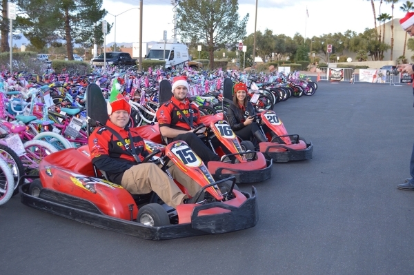 Pole Position Raceway þÄúelvesþÄù Keith Nicholson, Bryant Mark and Jessica Becerra pose inside the high performance electric go karts as they deliver 1,000 race passes during the ...