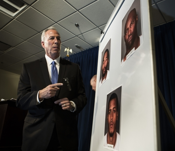 Clark County District Attorney Steve Wolfson points to pictures of  three  men  indicted in connection with a series of home invasions and sexual assaults during a press conference at  LVMPD Headq ...