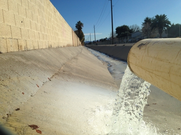 A steady stream of groundwater spills into the Rawhide storm channel at the corner of Lamb Boulevard and Rawhide Street on Tuesday. The water is being pumped from the ground by workers installing  ...