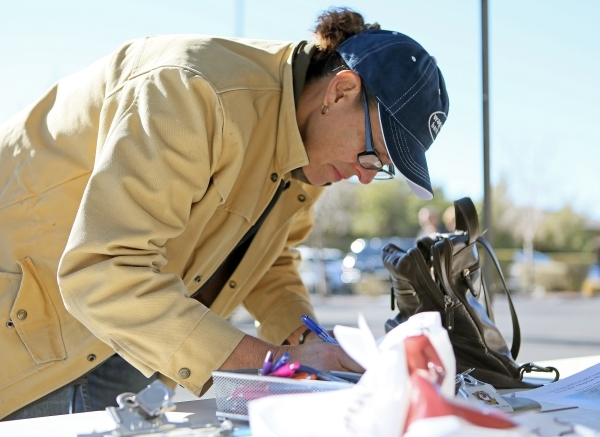 Valerie Juick fills out paperwork for the horse she purchased with a winning bid during an adoption event outside the Bureau of Land ManagementþÄôs Southern Nevada District Office on Satu ...