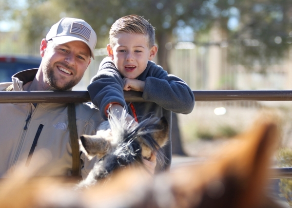 Justin Mackie, left, and his son Alexander, 7, pet Darcy Annie, a 4-month-old buckskin filly, during an adoption event outside the Bureau of Land ManagementþÄôs Southern Nevada District O ...