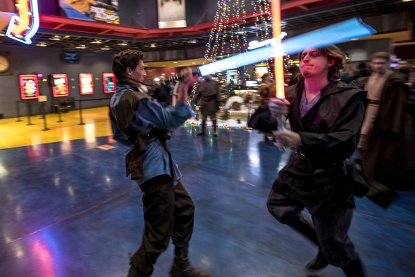 """Aryn Ross, left, and Evan Deiro battle with light sabers during opening night of """"Star Wars: The Force Awakens"""" at the Galaxy Theaters at the Cannery hotel-casino  in Las Vegas on Thursd ..."""