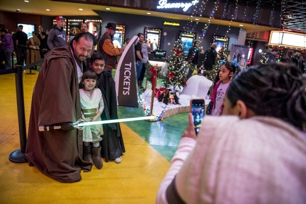 """Carlos Godinez, left, poses for a photo with Giulianna Levinne, 4, and Joshua Diaz, 7, during opening night of """"Star Wars: The Force Awakens"""" at the Galaxy Theaters at the Cannery hotel- ..."""