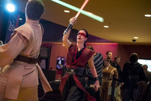 """Sean Ailshie, left, and Samantha Browne battle with light sabers during opening night of """"Star Wars: The Force Awakens"""" at the Galaxy Theaters at the Cannery hotel-casino  in Las Vegas o ..."""