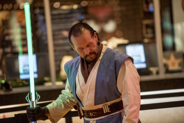 """Carlos Godinez holds a light saber during opening night of """"Star Wars: The Force Awakens"""" at the Galaxy Theaters at the Cannery hotel-casino  in Las Vegas on Thursday, Dec. 17, 2015. Jos ..."""