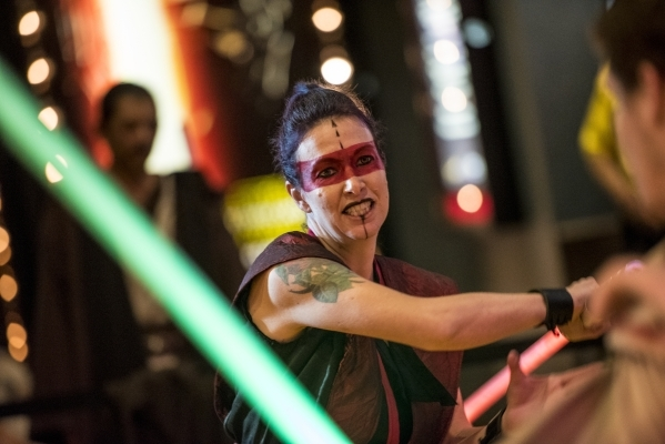 """Sean Ailshie, right, and Samantha Browne battle with light sabers during opening night of """"Star Wars: The Force Awakens"""" at the Galaxy Theaters at the Cannery hotel-casino  in Las Vegas  ..."""