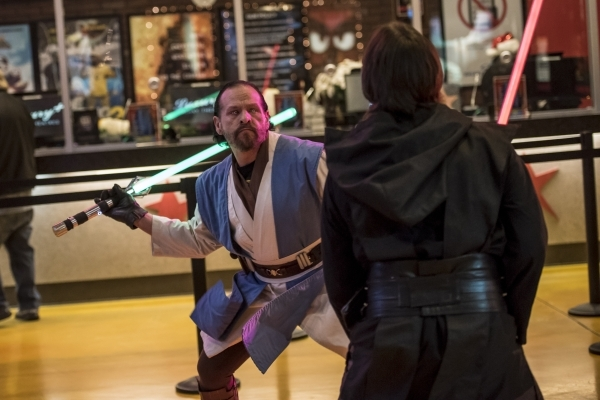 """Carlos Godinez, left, and Evan Deiro battle with light sabers during opening night of """"Star Wars: The Force Awakens"""" at the Galaxy Theaters at the Cannery hotel-casino  in Las Vegas on T ..."""