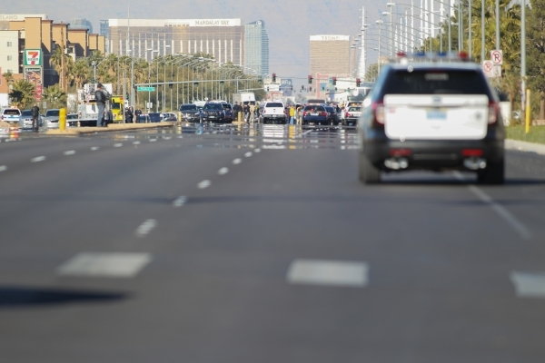 A Metro police interceptor drives to the scene as police look for the shooter of a Las Vegas police officer at the Emerald Suites, 9145 Las Vegas Blvd. South, near the intersection of Agate Avenue ...