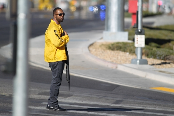 A Las Vegas Metro officer stands on Serene Avenue at Las Vegas Boulevard as police look for the shooter of a Las Vegas police officer at the Emerald Suites, 9145 Las Vegas Blvd. South, near the in ...