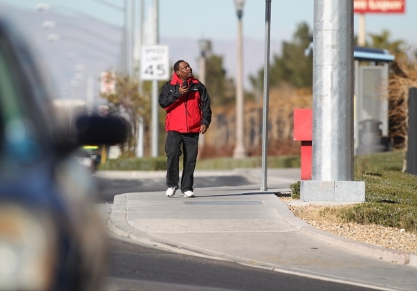 A pedestrian looks at a police helicopter as police look for the shooter of a Las Vegas police officer at the Emerald Suites, 9145 Las Vegas Blvd. South, near the intersection of Agate Avenue on T ...