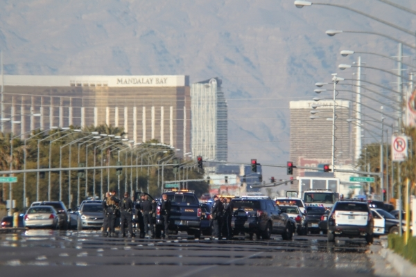 Police vehicles fill the scene as officers look for the shooter of a Las Vegas police officer at the Emerald Suites, 9145 Las Vegas Blvd. South, near the intersection of Agate Avenue on Thursday,  ...