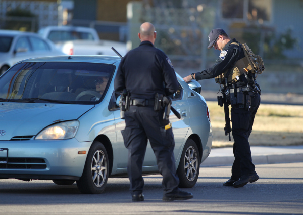 Police search cars at the corner of Richmar Avenue and Haven Street for the shooter of a Las Vegas police officer at the Emerald Suites, 9145 Las Vegas Blvd. South, near the intersection of Agate  ...