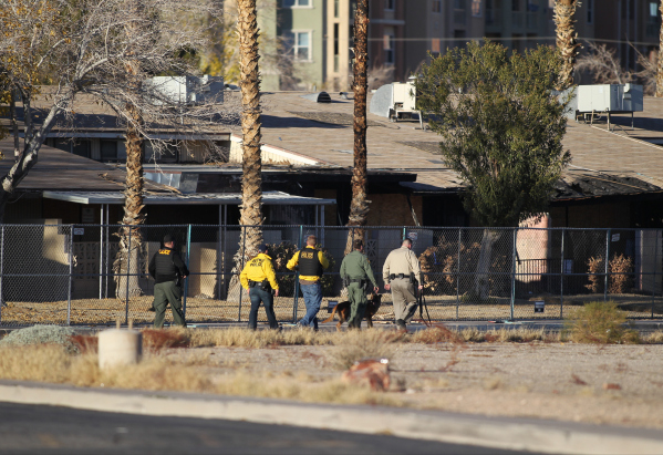 Police search a neighborhood on Richamar Avenue near Las Vegas Boulevard as they look for the shooter of a Las Vegas police officer at the Emerald Suites, 9145 Las Vegas Blvd. South, near the inte ...