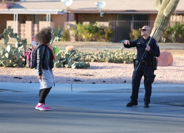 Police officers check cars and keep students out of the perimeter at the corner of Haven Street and Richmar Avenue as they look for the shooter of a Las Vegas police officer at the Emerald Suites, ...