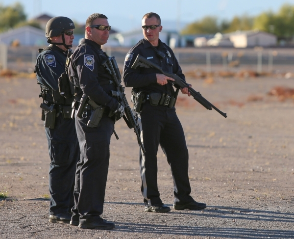 Nevada Highway Patrol officers stand in a lot off of Richmar Avenue near Las Vegas Boulevard as they look for the shooter of a Las Vegas police officer at the Emerald Suites, 9145 Las Vegas Blvd.  ...