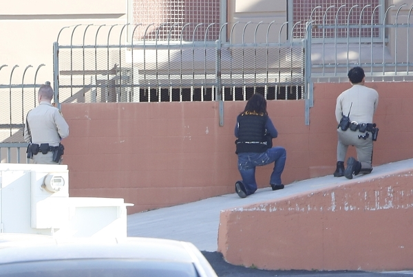 Las Vegas metro police officers take cover outside a south valley long-term motel as they are looking for the shooter of a Las Vegas police officer at the Emerald Suites, 9145 Las Vegas Blvd. Sout ...