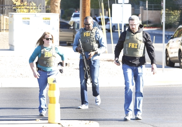 Members of the FBI arrive at a south valley long-term motel where a Las Vegas police officer was shot at the Emerald Suites, 9145 Las Vegas Blvd. South, near the intersection of Agate Avenue on Th ...
